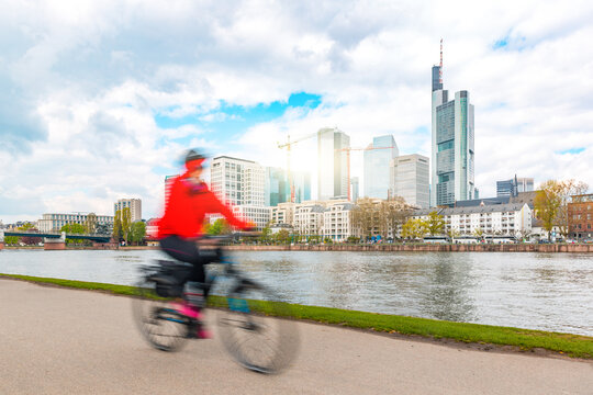 One person going by bike in Frankfurt, with financial downtown district on background - Sustainable commuting in the city, ecological transportation in Germany - Urban lifestyle concept