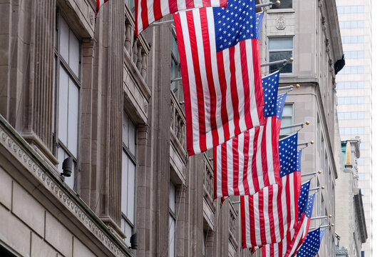 Low Angle View Of American Flags Against Buildings In City