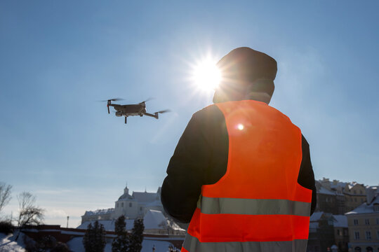 Close up picture of flaying quadrocopter dron and pilot siluette in sunset light and blue sky background, Man flying a drone in the city using a controller,