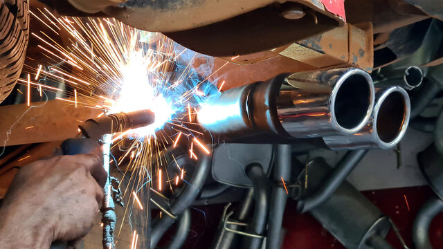 Mechanic or welder is fixing a car exhaust system by welding the exhaust pipe