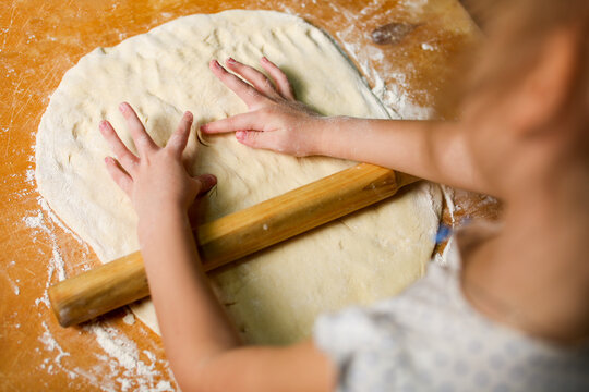 Children's hands on the dough, sculpt handprints. Preparation for baking, flour and wood board.