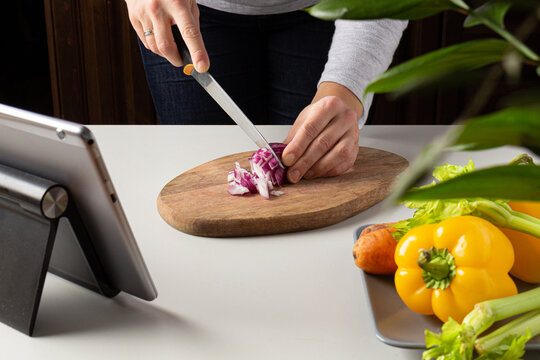 Woman cutting onion and watch virtual culinary class. Online cooking class