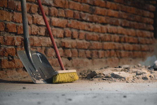 Shovel and broom on the dusty construction site floor background.