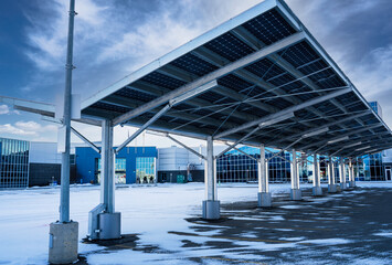 Obraz A solar carport for producing renewable energy and electric vehicle charging for a green alternative in Airdrie Alberta Canada. - fototapety do salonu