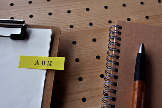 There is a notebook, a pen, and a clipboard with a sticky note stuck to it that says ABM written on it. It was an abbreviation for Account Based Marketing.