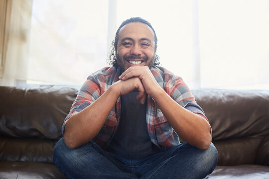 Smiling young latino man in his thirties sitting on his couch at home.