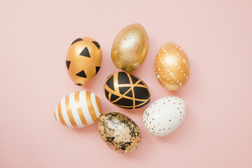 Easter golden decorated eggs on pastel pink background. Minimal easter concept. Happy Easter card...