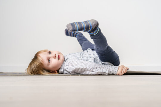 Full length portrait of small caucasian boy laying on the yoga mat on the floor with legs in the air - leisure activity growing up and childhood concept with copy space