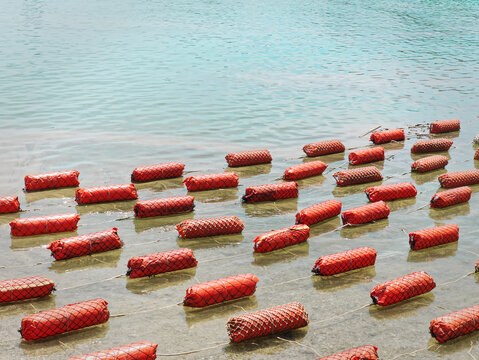 Group of Orange Shore Protective Floating Buoys on Sea Water Surface