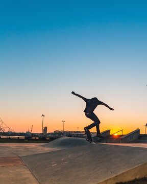 Rear View Of Man Skateboarding On Street Against Clear Sky During Sunset