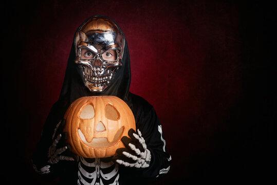 Portrait Of Boy Wearing Skull Mask While Holding Jack O Lantern Against Black Background