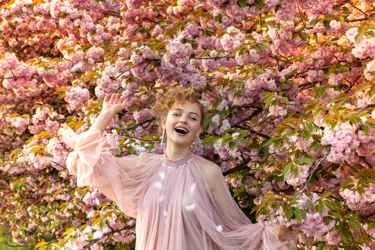 Very joyful young girl in a pink dress on a background of flowering sakura trees. Sincere emotions, laughter