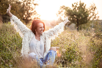 Happy Mature Woman Sitting With Arms Outstretched On Field