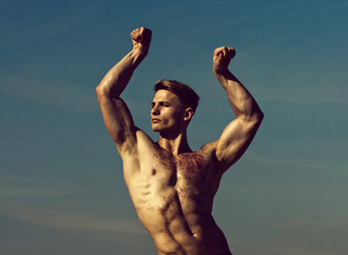 Man with glitter on bare chest. Athletic bodybuilder pose as hercules. Gladiator or atlant. Man with muscular wet body.