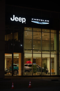 Chelyabinsk, Russia - September 29, 2020: JEEP  Company logo on the dealership building at night. Jeep is a subsidiary of Fiat Chrysler Automobiles and produces sport car. Vertical photo
