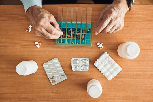 Senior man organizing his medication into pill dispenser. Senior man taking pills from box. Healthcare and old age concept with medicines. Medicaments on table