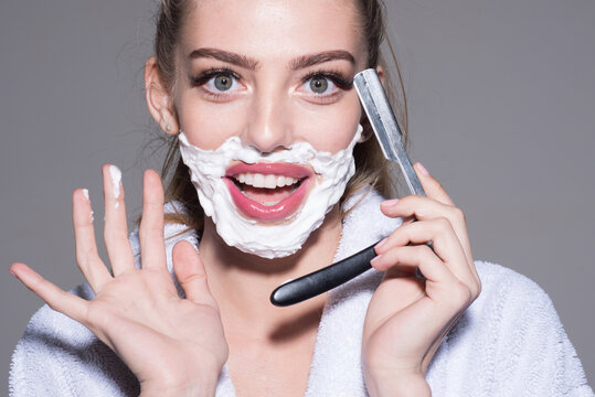 Woman with sharp blade of straight razor. Barber and shaving concept. Female barber shaving face in barber shop.