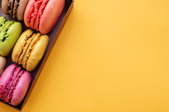 Colorful macaroons. Sweet pasta on a yellow background with copy space. Top view, holiday time concept