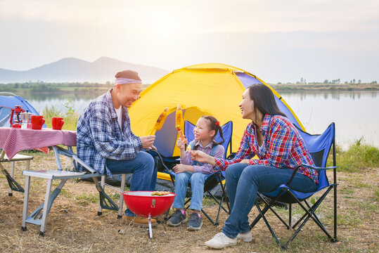Group of asian family grilling sweet corn and BBQ on stove at camping site, everyone feeling happy. Family outdoor activity concept.