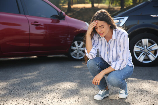 Stressed woman near cars after traffic accident outdoors