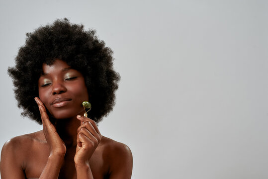 Portrait of relaxed young african american woman with perfect glowing skin massaging her face with jade roller, posing with eyes closed isolated over gray background
