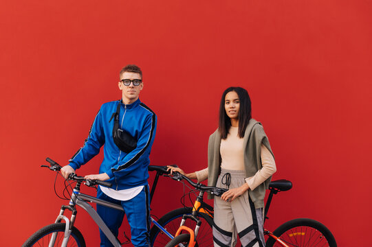 Stylish young people in sportswear with bicycles isolated on red background, looking at the camera and smiling. Cycling concept.