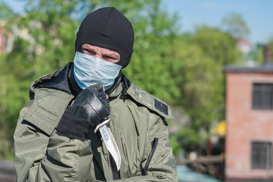 Pensive criminal with a knife in a medical mask and balaclava squints his eyes because of the bright sun