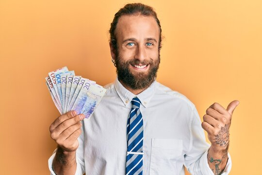Handsome man with beard and long hair holding swedish krona banknotes pointing thumb up to the side smiling happy with open mouth