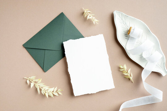 Wedding stationery top view. Flat lay blank white invitation card, green envelope, wedding decorations, silk ribbon and dried flowers on pastel beige background.
