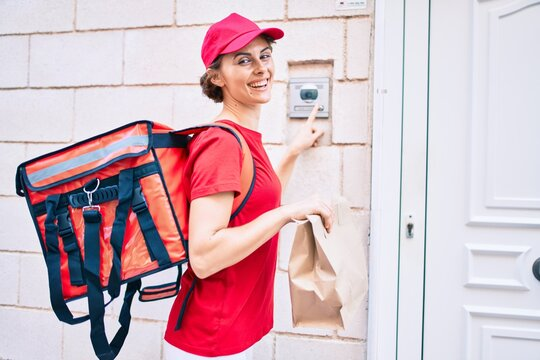 Delivery business worker woman wearing uniform smiling happy knocking on the door