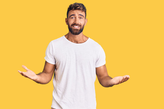 Young hispanic man wearing casual white tshirt clueless and confused expression with arms and hands raised. doubt concept.