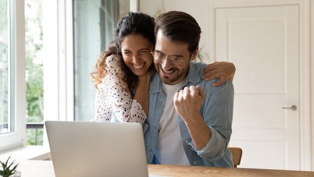 Laughing excited millennial family couple embracing by computer screen winning prize at lottery or sports betting. Loving young wife sharing amazed husband joy of getting reward perfect job proposal