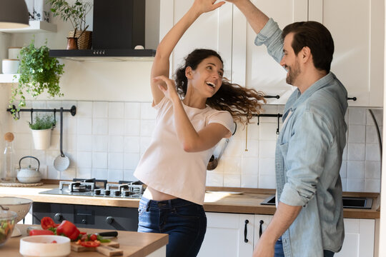 Romantic young spouses arrange disco party for two on quarantine at kitchen. Excited family couple in love having fun dancing waltz listen to music relaxing resting from everyday cooking food routine