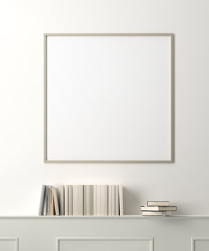 Blank picture frame mockup above wood paneled wall with books.