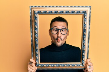Handsome man with tattoos holding empty frame making fish face with mouth and squinting eyes, crazy...