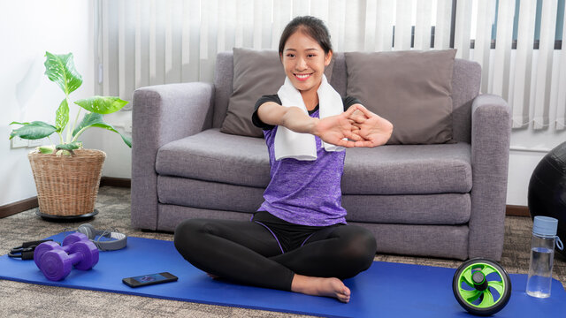 sporty woman in sportswear is sitting on mat at home in the living room exercising, healthy and  lifestyle concept.