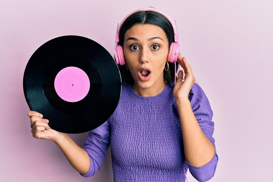 Young hispanic woman using headphones holding vinyl disc afraid and shocked with surprise and amazed expression, fear and excited face.