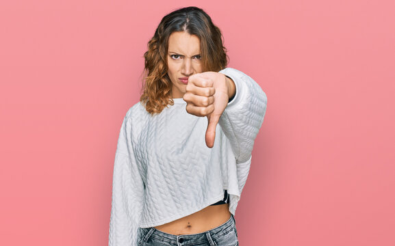 Beautiful young caucasian woman wearing casual winter sweater looking unhappy and angry showing rejection and negative with thumbs down gesture. bad expression.