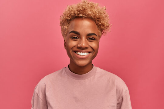 Studio portrait of young dark skinned woman with blonde hair in good mood standing on pink background. Joyful woman posing in studio expressing happiness. Concept of happiness and positive emotions.
