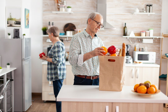 Senior couple arriving from supermarket with grocery bag and unpacking in kitchen early in the morning. Elderly retired persons enjoying life, spending time together helping each other