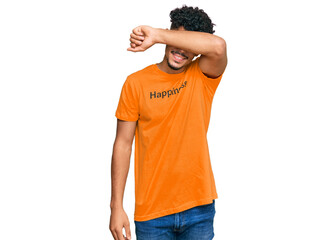 Young arab man wearing tshirt with happiness word message smiling cheerful playing peek a boo with hands showing face. surprised and exited Wall mural