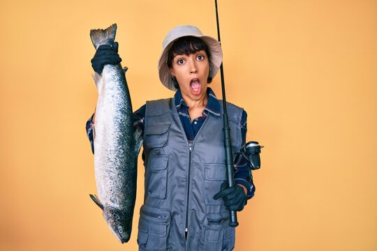 Beautiful brunettte fisher woman holding fishing rod and raw salmon in shock face, looking skeptical and sarcastic, surprised with open mouth