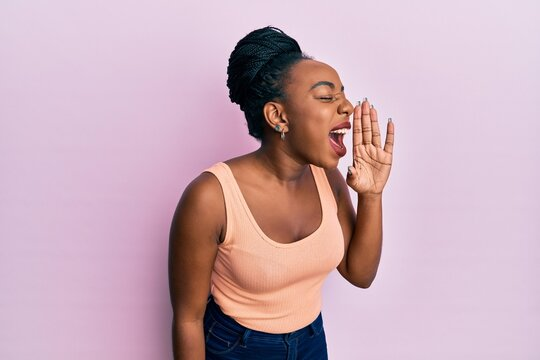 Young african american woman wearing casual style with sleeveless shirt shouting and screaming loud to side with hand on mouth. communication concept.