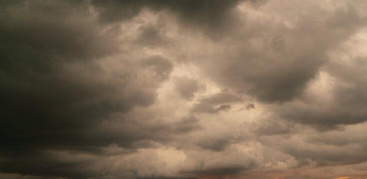 Dark storm cloud Rain clouds in sunset or sunrise sky Dramatic black cloudscape in bad weather day