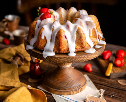 tasty homemade bundt cake with strawberries and white glaze on top on wooden cake stand on rustic table
