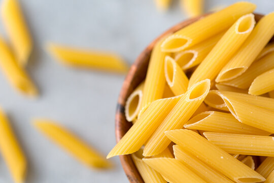 Uncooked yellow pasta on gray table from above. Selective focus. Italian food concept.