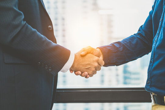 Midsection Of Business People Shaking Hands In Office