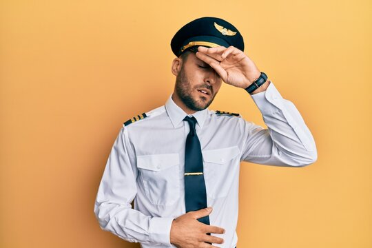 Handsome hispanic man wearing airplane pilot uniform touching forehead for illness and fever, flu and cold, virus sick