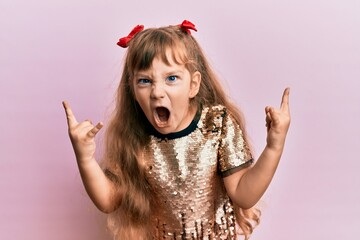 Little caucasian girl kid wearing festive sequins dress shouting with crazy expression doing rock...