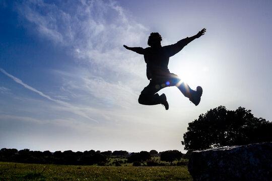 silueta de Hombre joven saltando con el cielo azul de fondo por detras